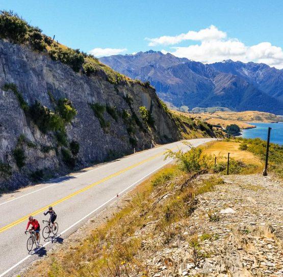 Bikers on road through mountains on New Zealand Bike Tour