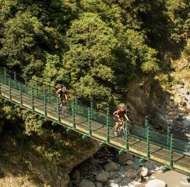 Bikers crossing bridge on Taiwan Bike Tour