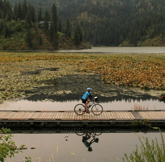 Biker on pond on Trail of the Coeur d'Alenes tour