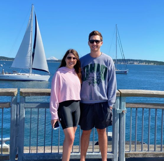 A couple in front of a sailboat in Puget Sound