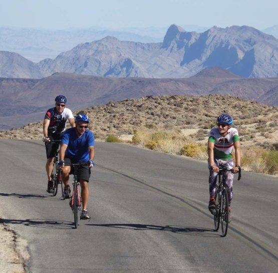 Three people cycling on an empty road through the desert in Nevada