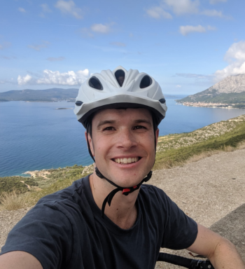 Man in blue t-shirt and a white bike helmet with lake in the background